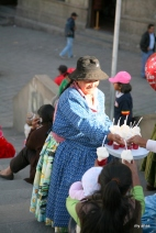 A cholita handing out drinks in Plaza San Francisco.